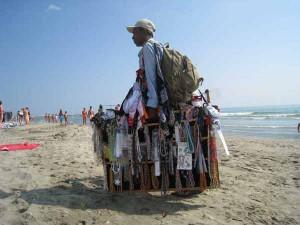 Ambulante in spiaggia con la sua merce